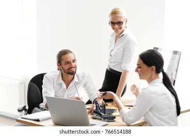 Team Working In Office, Looking At Computer. Smiling Business People Brainstorming, Sitting At Conference Table With Notebook And Sharing Ideas At Project Meeting. High Resolution.