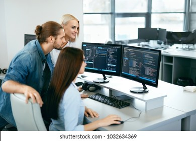 IT Team Working In Office. People Programming On Computer. Young Programmers Typing Data Code On Keyboard At Workplace, Looking At Computer Monitors In Modern Office. High Quality