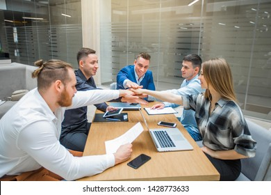 team of young adult people managers at work indoors hold hands