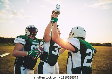 Team of young American football players celebrating victory and raising a championship trophy together after a game