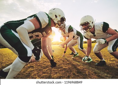 Team of young American football players lining up in formation during an afternoon practice session