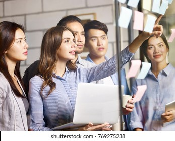 team of young asian and caucasian entrepreneurs discussing business using laptop, digital tablet and adhesive notes in office.
