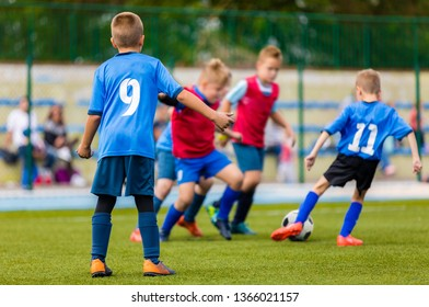 Team of young boys running through green pitch during tournament football match. Children kids having fun playing soccer game outdoor. Soccer season for kids