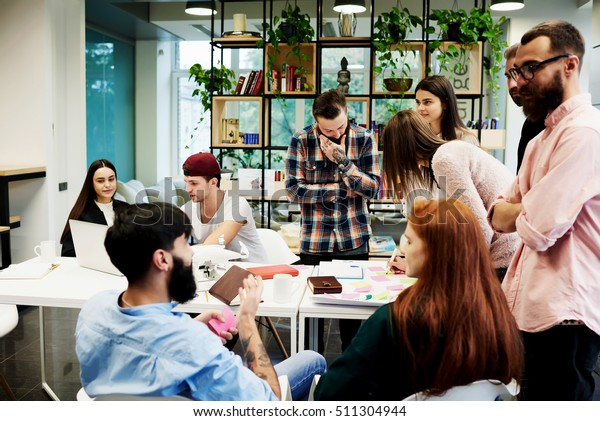 Team of young business professionals using technology in an informal meeting engaged on architect design. International students learning together in university library. Concept of successful startup