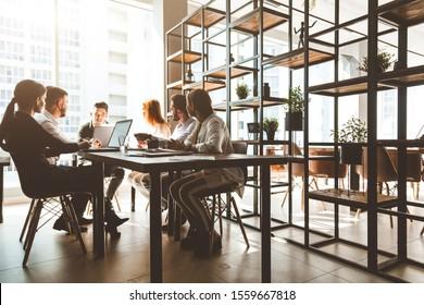 Ein Team junger Geschäftsleute, die in einem Büro zusammenarbeiten und kommunizieren. Firmenmanager und Geschäftsführer in einem Meeting.