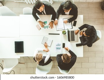 A team of young businessmen working and communicating together in an office. Corporate businessteam and manager in a meeting.