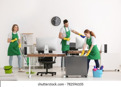 Team of young cleaning service professionals at work in office