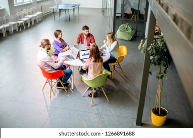 Team of a young coworkers dressed casually working together with laptops sitting at the round table in the office, wide view on the office from above
