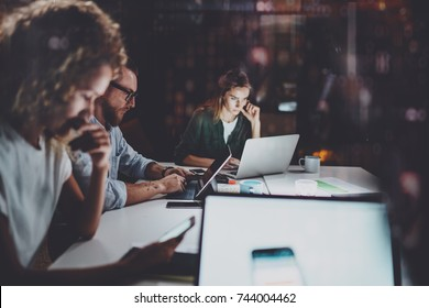 Team of young coworkers work together at night office.Young people using electronic laptops at the table.Horizontal.Blurred background