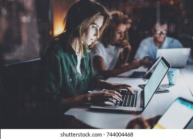 Team of young coworkers working together at night office.Young woman using mobile laptop at the table.Horizontal.Blurred background