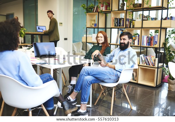 Team of young creative marketing experts brainstorming during working on advertising strategy for company sharing ideas on conference using technology and wireless connection in modern designed office