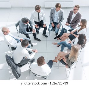 team of young employees sitting in a circle in the conference room .