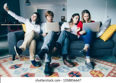 Team of young entrepreneurs working in informal settings. Four people sitting on couch together and using gadgets. Team job concept