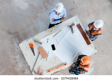 Team of young man and woman engineer and architects working, meeting, discussing,designing, planing, measuring layout of building blueprints in construction site floor at factory, top view. copy space