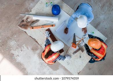 Team von jungen Mann und Frau Ingenieurinnen und Architekten arbeiten, treffen, diskutieren, gestalten, planen, messen die Anordnung der Baupläne im Baustellenboden in der Fabrik, Draufsicht. Kopienraum