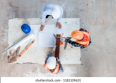 Team of young man and woman engineer and architects working, meeting, discussing, designing, planing, measuring layout of building blueprints in construction site floor at factory. Top view.