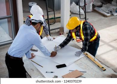 Das Team junger Ingenieure, Architekten und Helmhelmer arbeiten, treffen, diskutieren, gestalten, planen, messen die Anordnung der Baupläne vor dem Bau vor Ort.