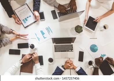 Ein Team junger Büroangestellter, Geschäftsleute mit Laptop arbeiten am Tisch und kommunizieren in einem Büro miteinander. Firmenmanager und Geschäftsführer in einem Meeting. Zusammenarbeit.