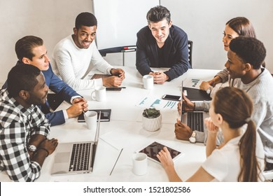 A team of young office workers, businessmen with laptop working at the table, communicating together in an office. Corporate businessteam and manager in a meeting. coworking.