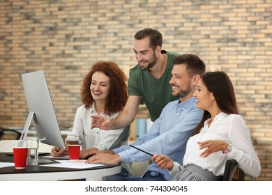 Team of young professionals working at table in office