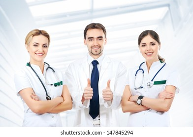 Team of young and smart medical workers over abstract hospital background