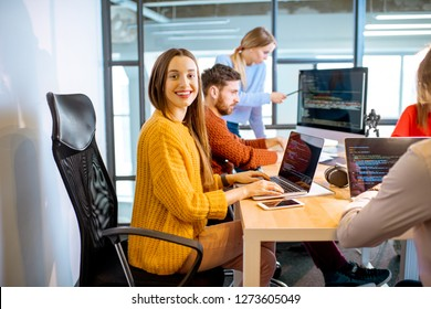 Team of a young woman as a programmer sitting in the office with people working on the background