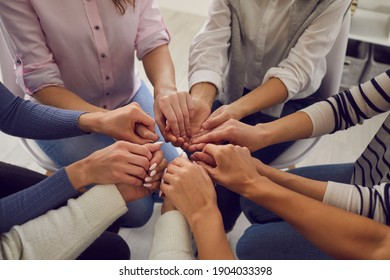 Team of young women sitting together and holding hands, demonstrating unity and solidarity. Group of people in community meeting thanking each other for help, support and true friendship