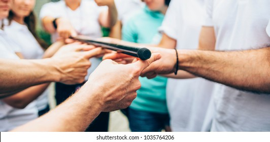 teambuilding activity with stick and hands
