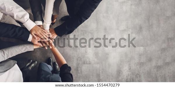 Teambuilding-Konzept. Geschäftsteam, das seine Hände zusammenlegt, Draufsicht, freier Raum, Panorama