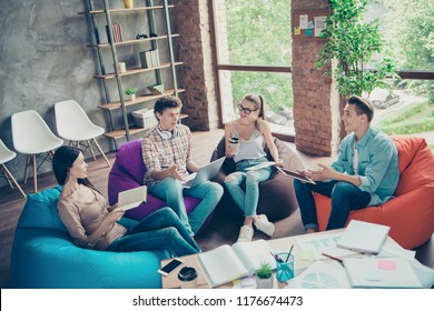 Teambuilding concept! Group of youth guy and cheerful girls sit in chairs bags near the table with documents and schedules and preparing for the final exam
