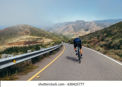 Teammates cycling, cyclist bunch riding together and descending narrow one lane road into the fog in marin county, just north of San Francisco, california.