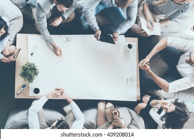 Teamwork in action. Directly above shot of business people sitting around desk and looking at copy space on large blank paper