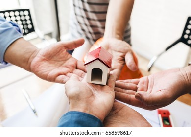 Teamwork of architectural engineer consulting on the creation of a model home, hands pointing to mini house toy model.
