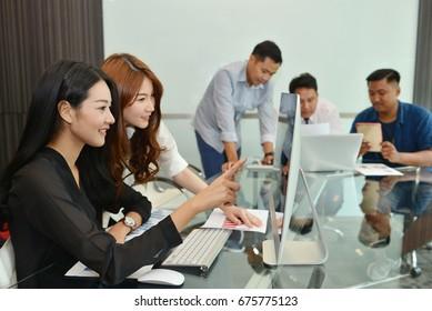 Teamwork of Asian business people having a meeting, working in boardroom