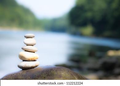 Teamwork balance concept. Balance stone on river coast