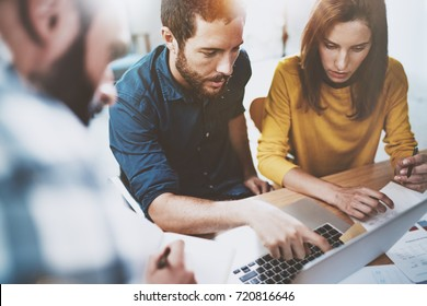 Teamwork business concept.Young Coworkers sitting at meeting office and using laptop.Horizontal.Blurred background.Cropped