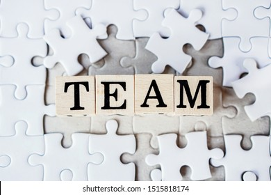 teamwork for business,finance and marketing concept with text on jigsaw puzzle background