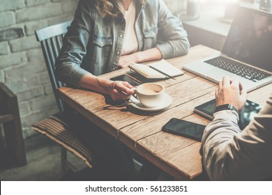 Teamwork. Businessman and businesswoman sitting at table in coffee shop and discuss business plan. On table is laptop, tablet, smartphone, notebook, cup of coffee.Business meeting of partners in cafe.