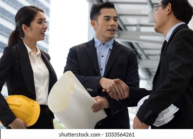 teamwork of bussiness and engineering shaking hand, after successful bussiness and construction