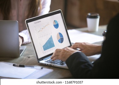 Teamwork. Close up of businessman and businesswoman working on laptop. Graph, chart and diagram on PC screen. View over the shoulder