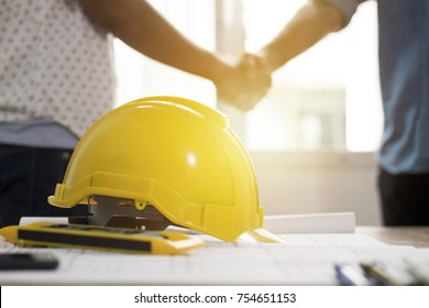 Teamwork concept, Architecture team shaking hand in building constraction, focus at yellow helmet