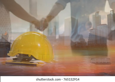 Teamwork concept, Architecture team shaking hand in building constraction, focus at safty helmet , mixed media