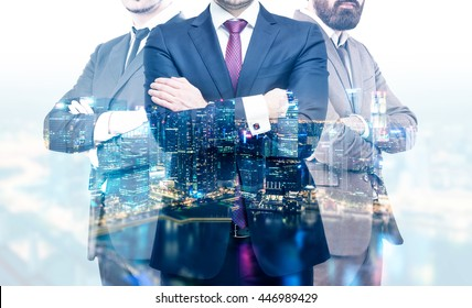 Teamwork concept with businesspeople crossing arms on night Singapore city background. Double exposure
