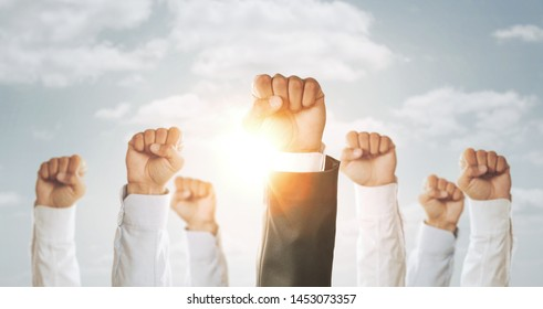 Teamwork concept, close up of group of business people fists raised up in the air over the sky background