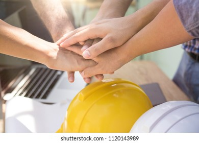 teamwork concept engineers and worker put hand on together on working table for powerful working