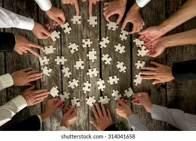 Teamwork Concept - High Angle View of Businessmen Hands Forming Circle and Holding Puzzle Pieces on Top of a Rustic Wooden Table.