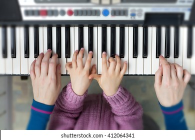 Teamwork Concept Image - Piano Keyboard top View and Hands of Child and Mother playing music