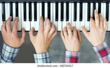 Teamwork Concept Image - top View of Piano Keyboard and male and female Hands playing music together four handed