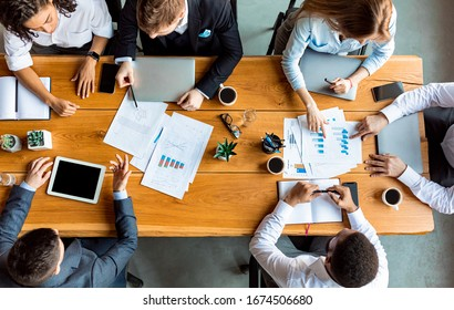 Teamwork Concept. Mixed Business Team Working Together Sitting At One Table In Modern Office. Above View