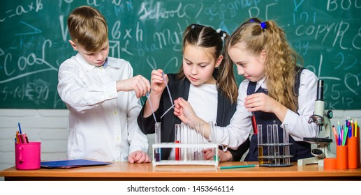 Teamwork concept. Test tubes with colorful liquid substances. Study of liquid states. Group school pupils study chemical liquids. School laboratory. Girls and boy conduct experiment with liquids.